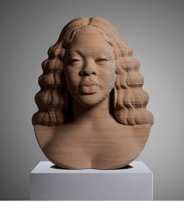 Breonna Taylor Bust Sculpture Looking Forward. Made of layered wood on a white marble base.