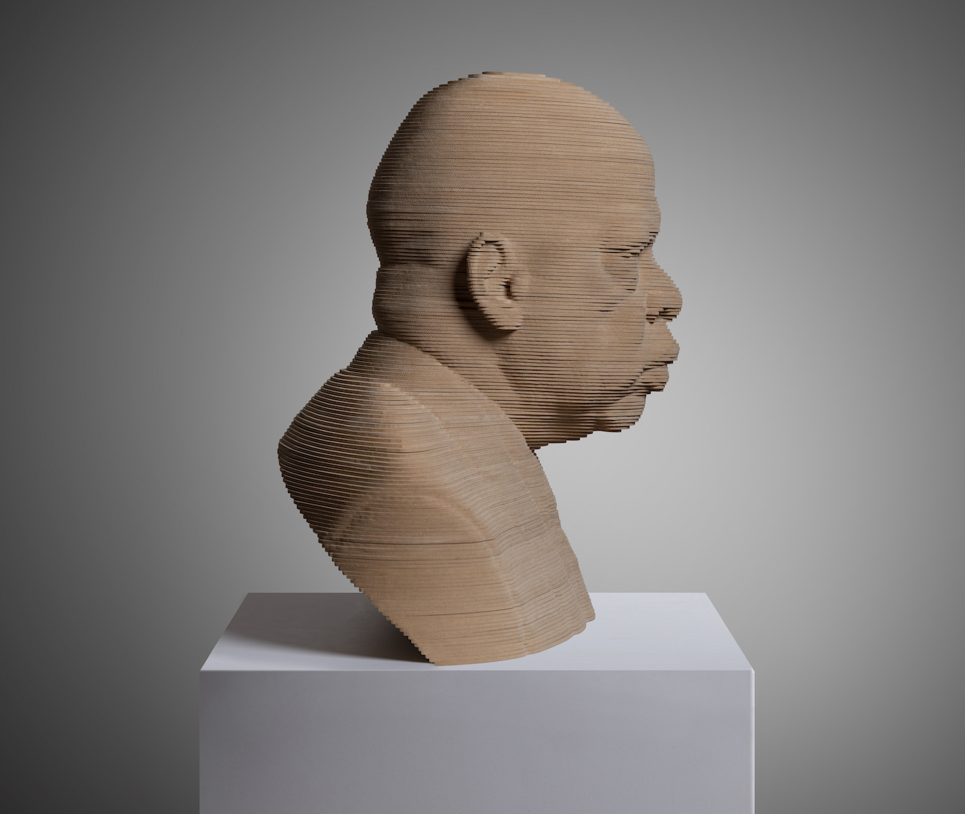 Senator John Lewis Bust Sculpture Looking Right. Made of layered wood on a white marble base.