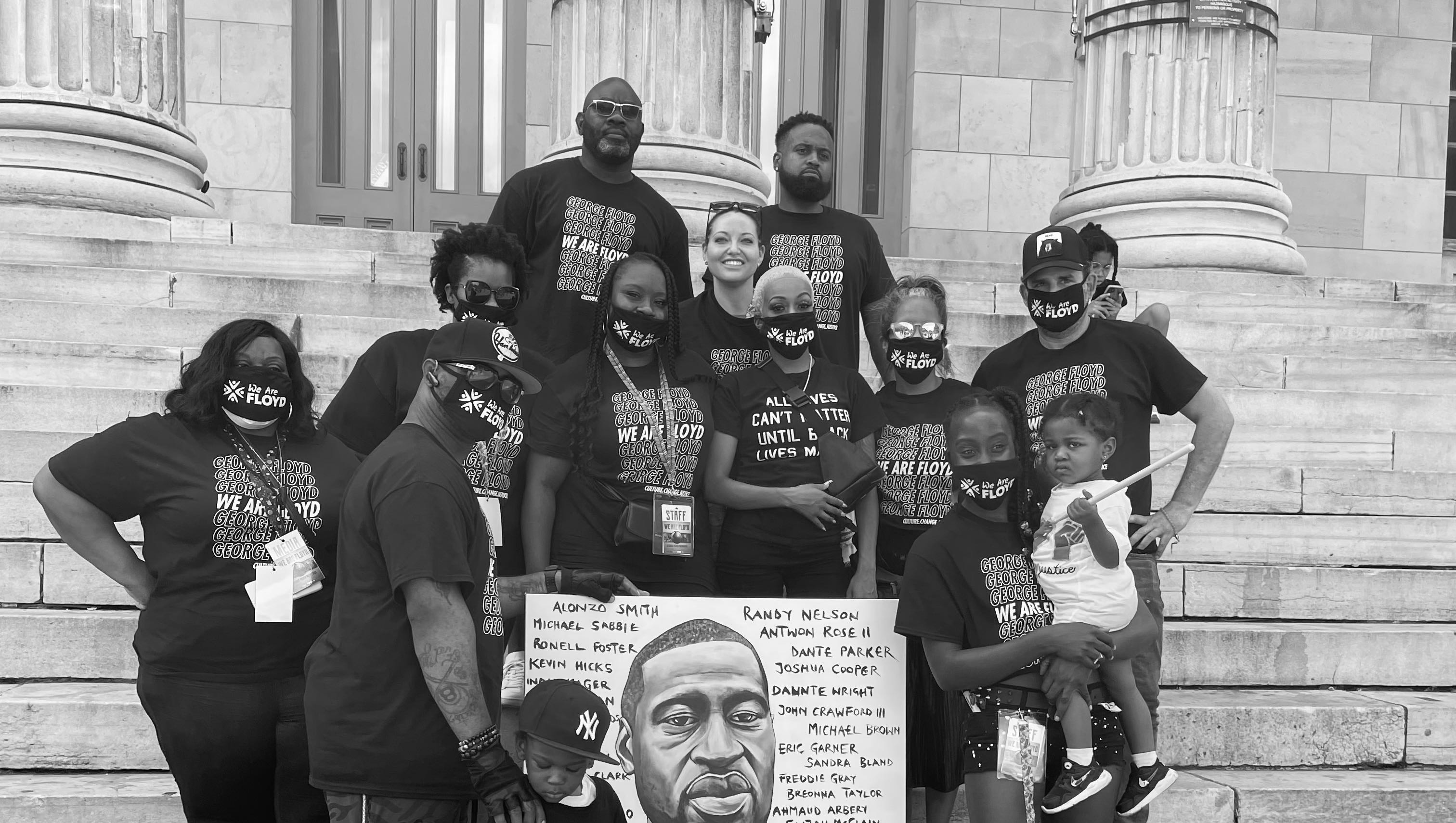 Black and White Group photo of the We Are Floyd and Confront Art members on the steps of a building with stone pillars. Artwork of George Floyd is held in the center of the photo.