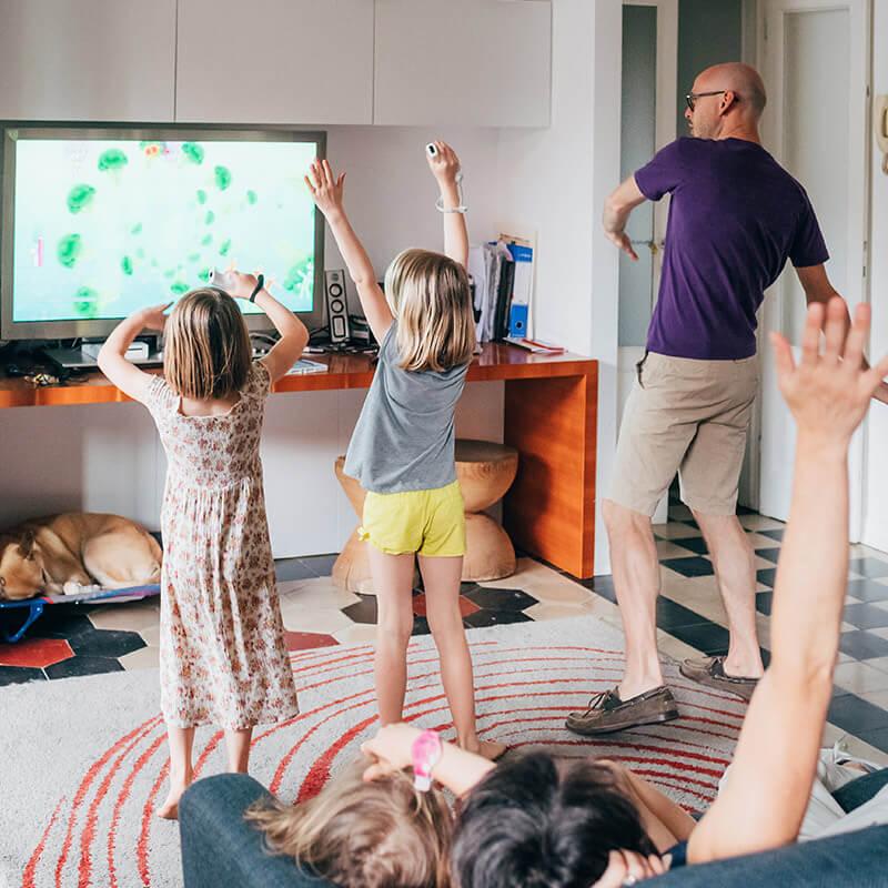 Familie spielt gemeinsam ein Videospiel und stehen vor dem TV-Gerät