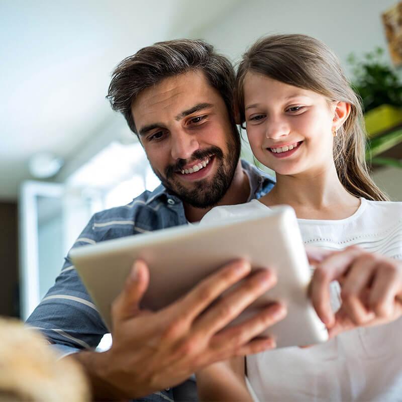 Vater und Tochter schauen gemeinsam auf ein Tablet