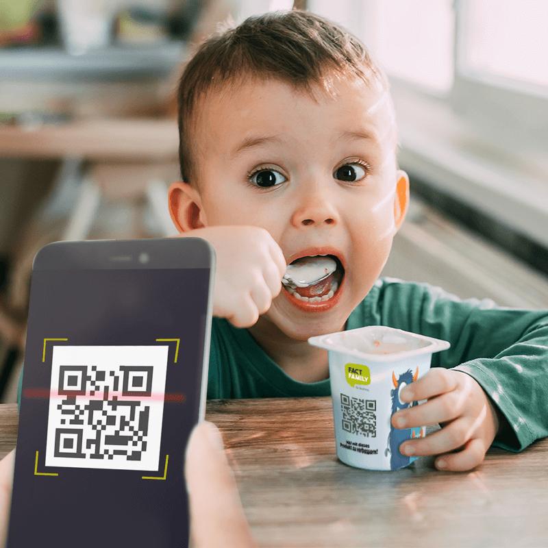 Ein Junge isst einen Joghurt mit einem QR-COde darauf