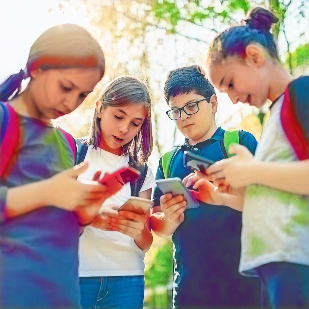 Vier Kinder stehen im Kreis und schauen auf Ihre Smartphones