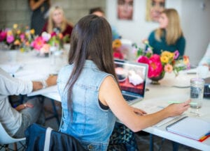 my board wants a local consultant to help plan a great nonprofit staff retreat means focusing in on the details. In this photo, a woman in a denim vest has her back to the camera. She's in front of her laptop at a white table with vases of flowers and other people across from her.