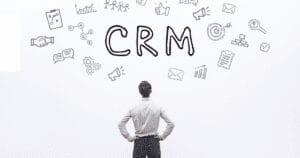 books on nonprofit marketing CRM with man staring up at the word CRM, surrounded by A LOT of options. You need a CRM for your nonprofit, and you need to know how to choose the best one.
