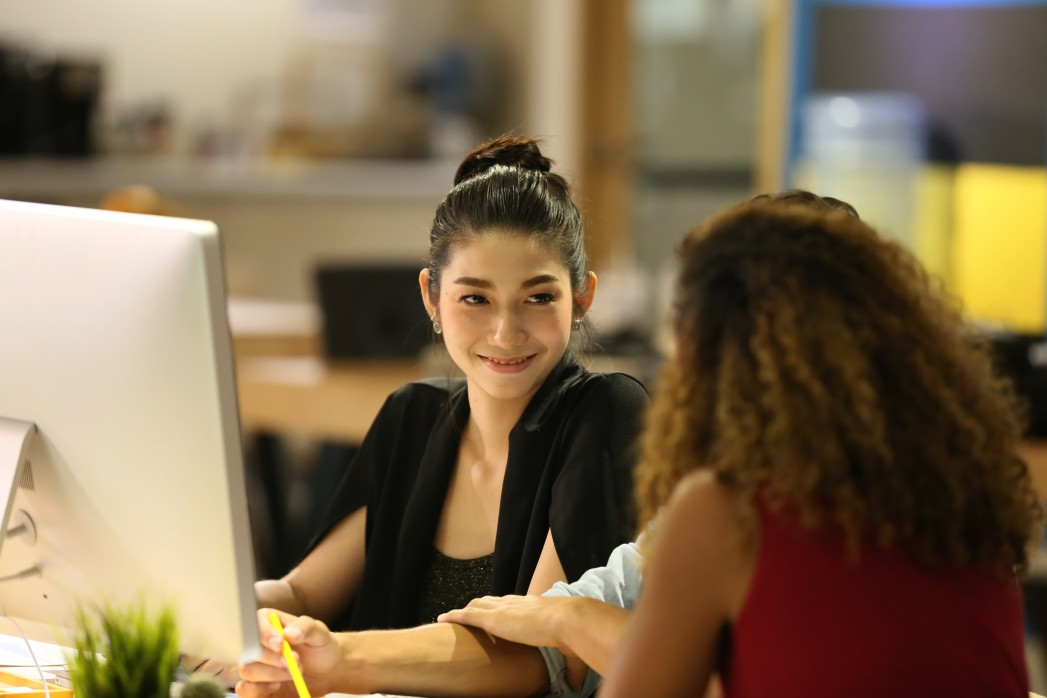 Two women sit a desk. One is in front of a computer. She is smiling at the other woman, her nonprofit career coach.
