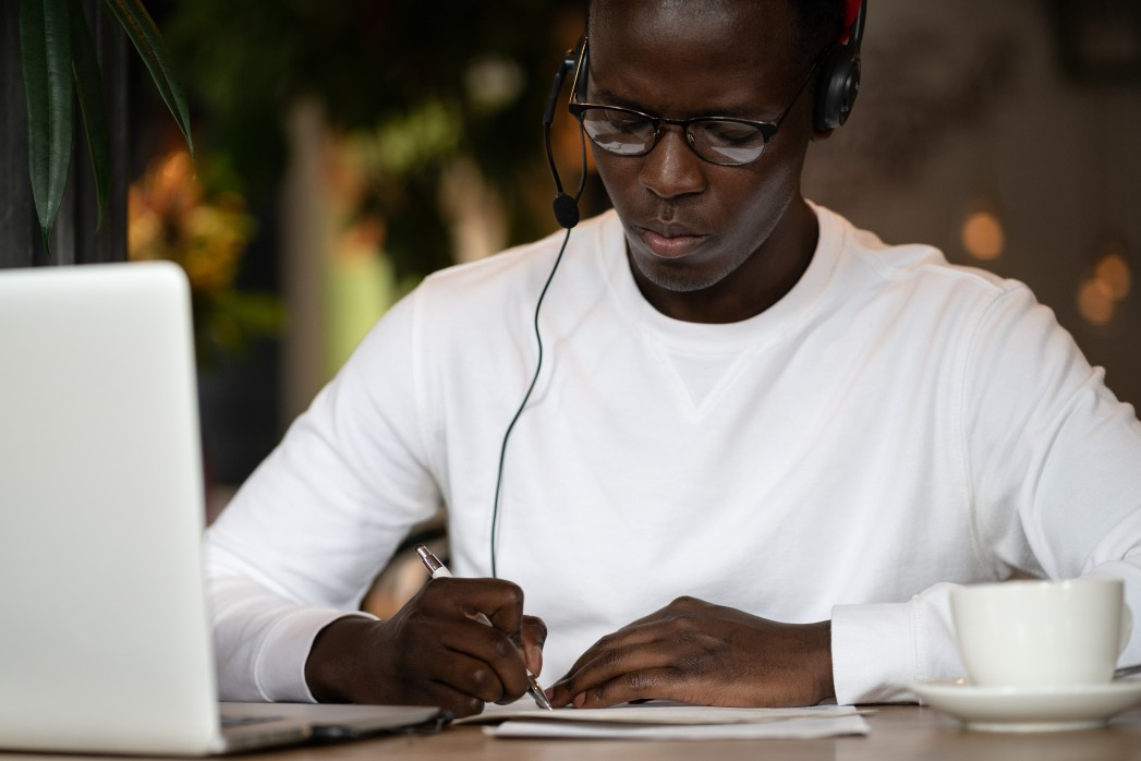 A man sits in front of his laptop, wearing earbuds, pen in hand. He looks serious -- maybe because he's measuring his nonprofit's impact!