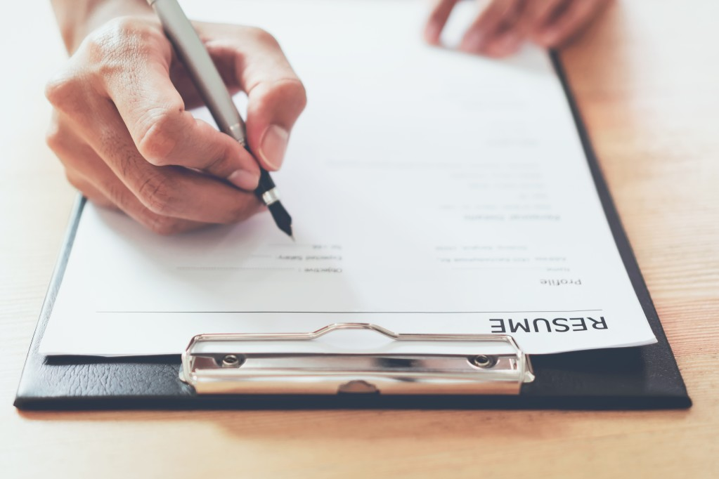 A hand holds a pen above a black clipboard with a piece of paper that says 'resume' on it. When you base your nonprofit interview questions on a candidate's resume, you'll have the best chance of getting to know them.