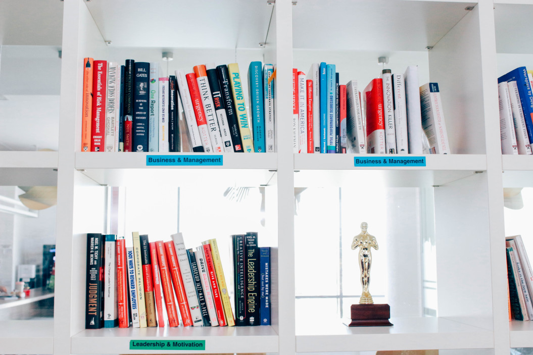 A glossy white bookcase with open cubbies is full of books on nonprofit marketing. There is a sole, gold trophy on a small wooden base on a shelf in the lower right corner.