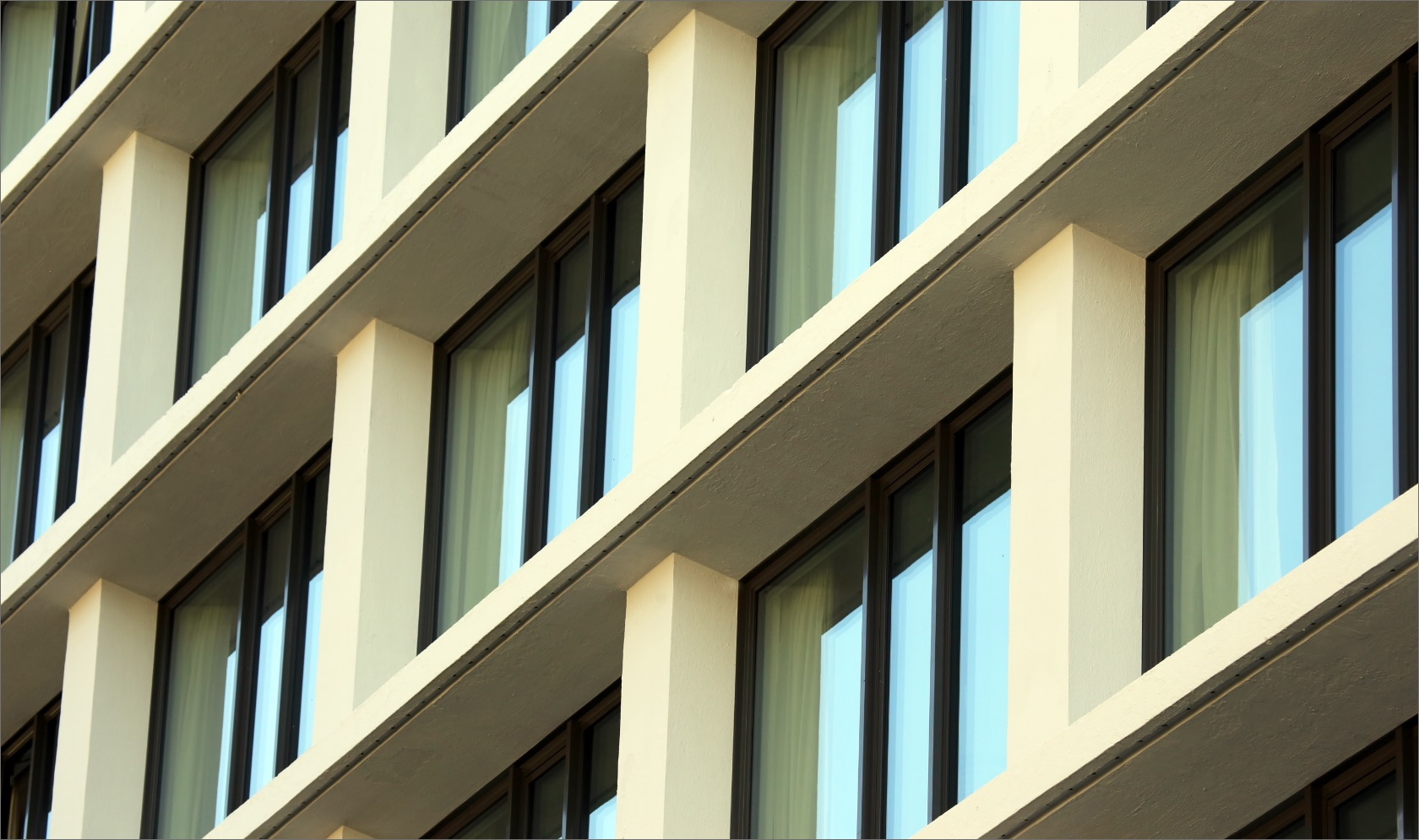 Modern sand colour block of flats facade with a glass