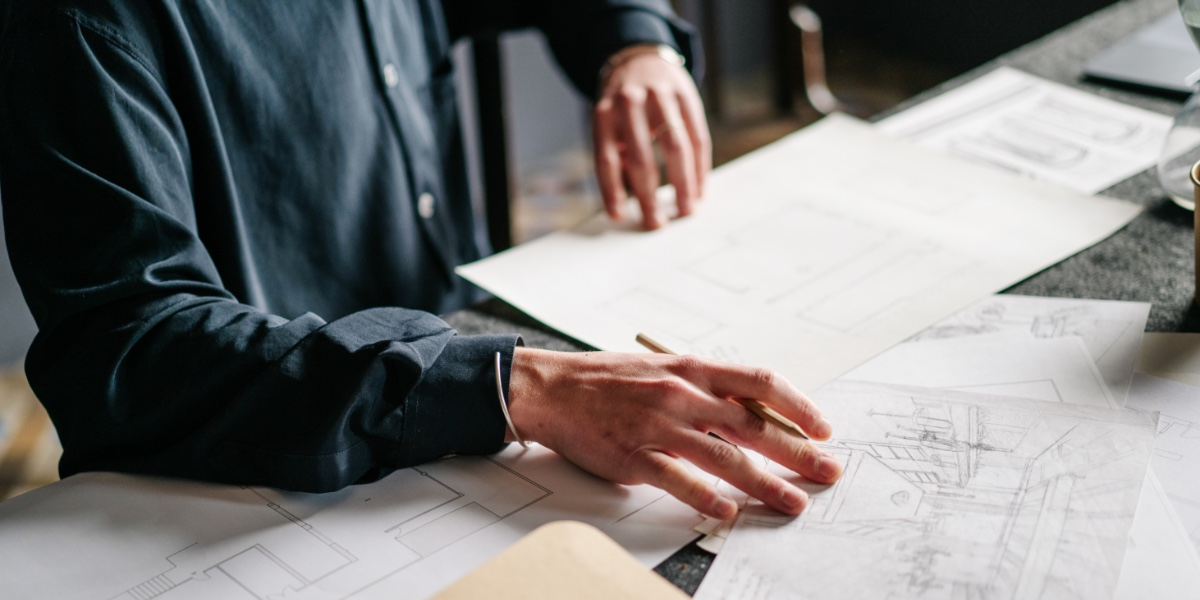 Person hand on a desk overlooking documents