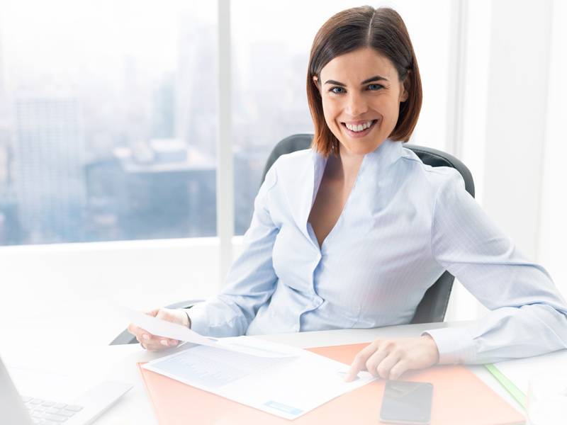 Lady sitting at a table looking into the camera smiling