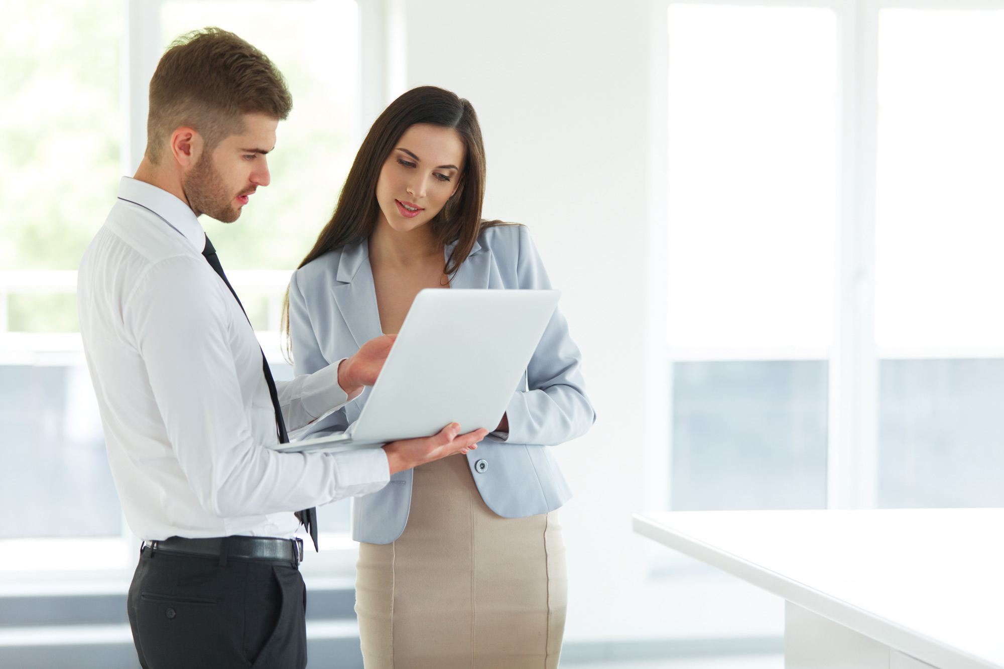 Two people reading a paper report