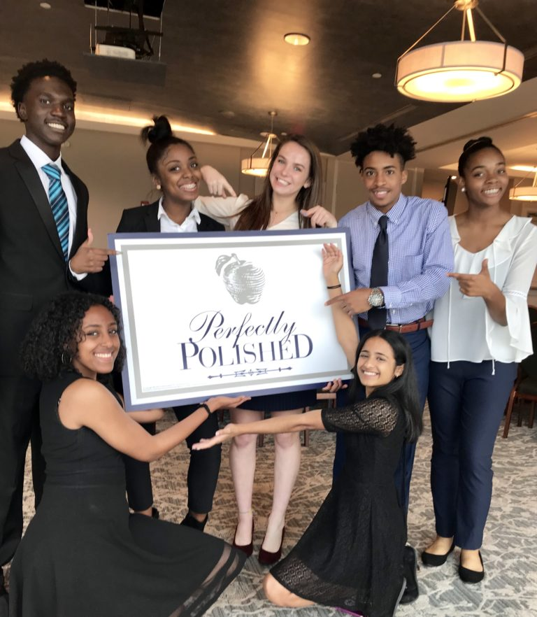 Young adults at leadership event holding a Perfectly Polished sign