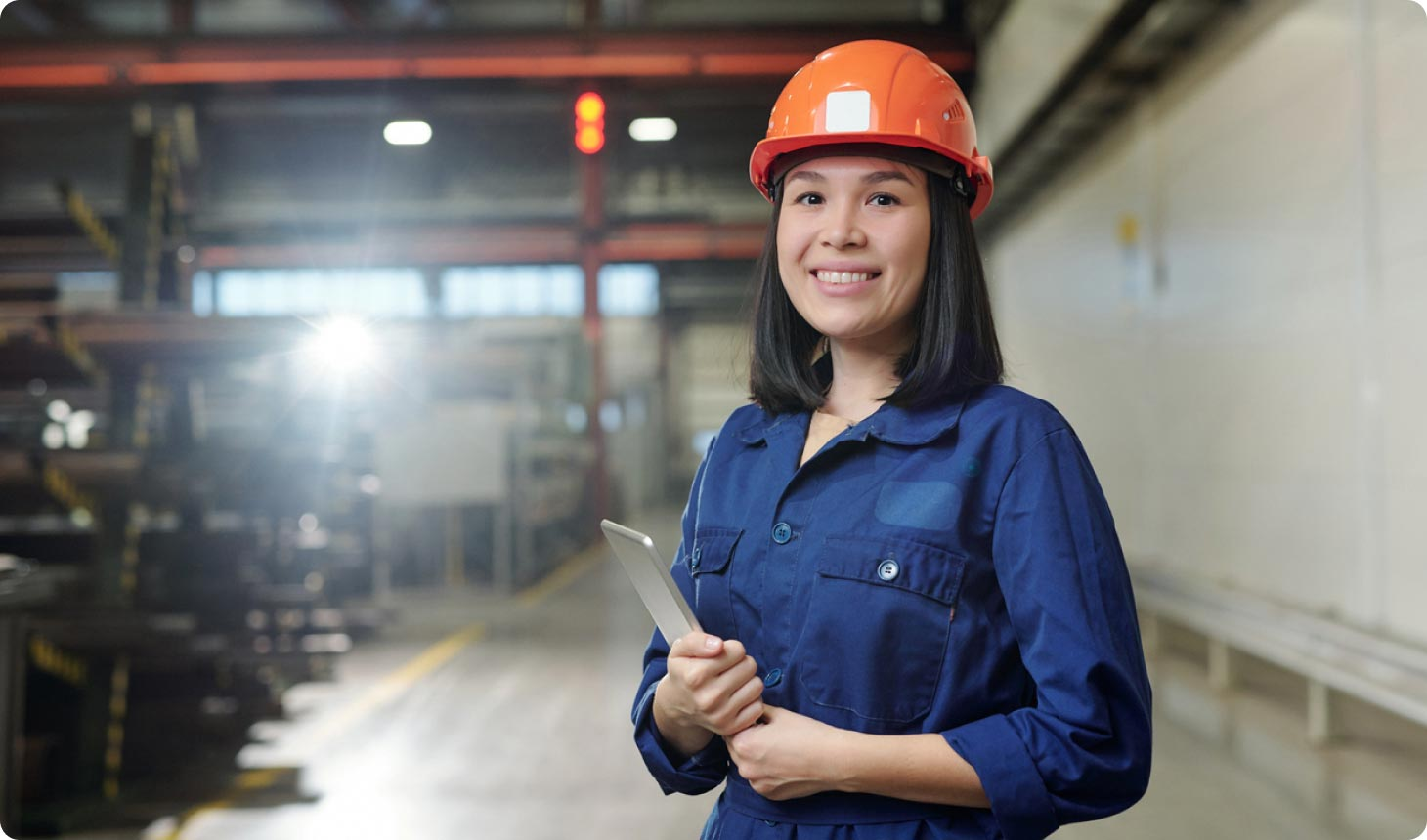 A female employee working in a warehouse holding a tablet