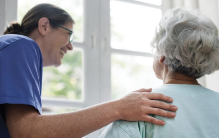 An aged care worker chats with a resident in a bright facility