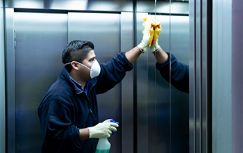 man cleaning an elevator with a facemask and heavy gloves, staring at his reflection