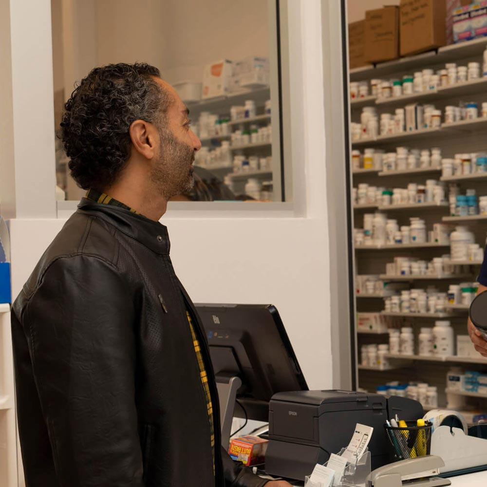 Customer picking up medications at PureCare Pharmacy in San Diego, CA.