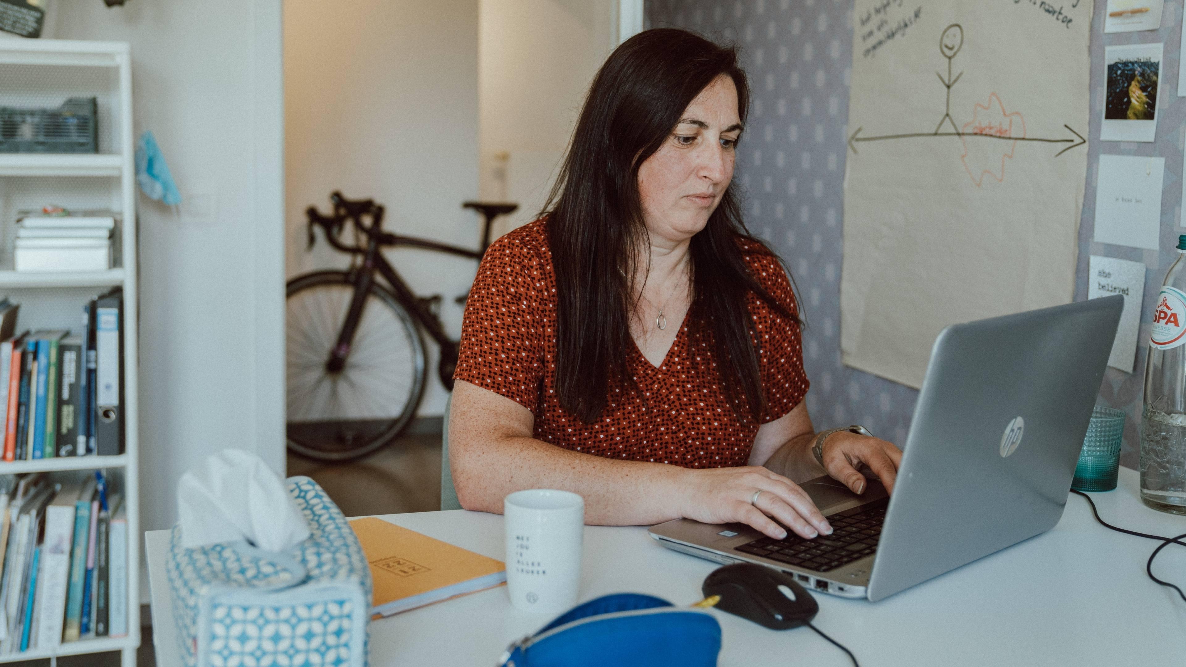 Vrouw die zit te werken en fiets op de achtergrond