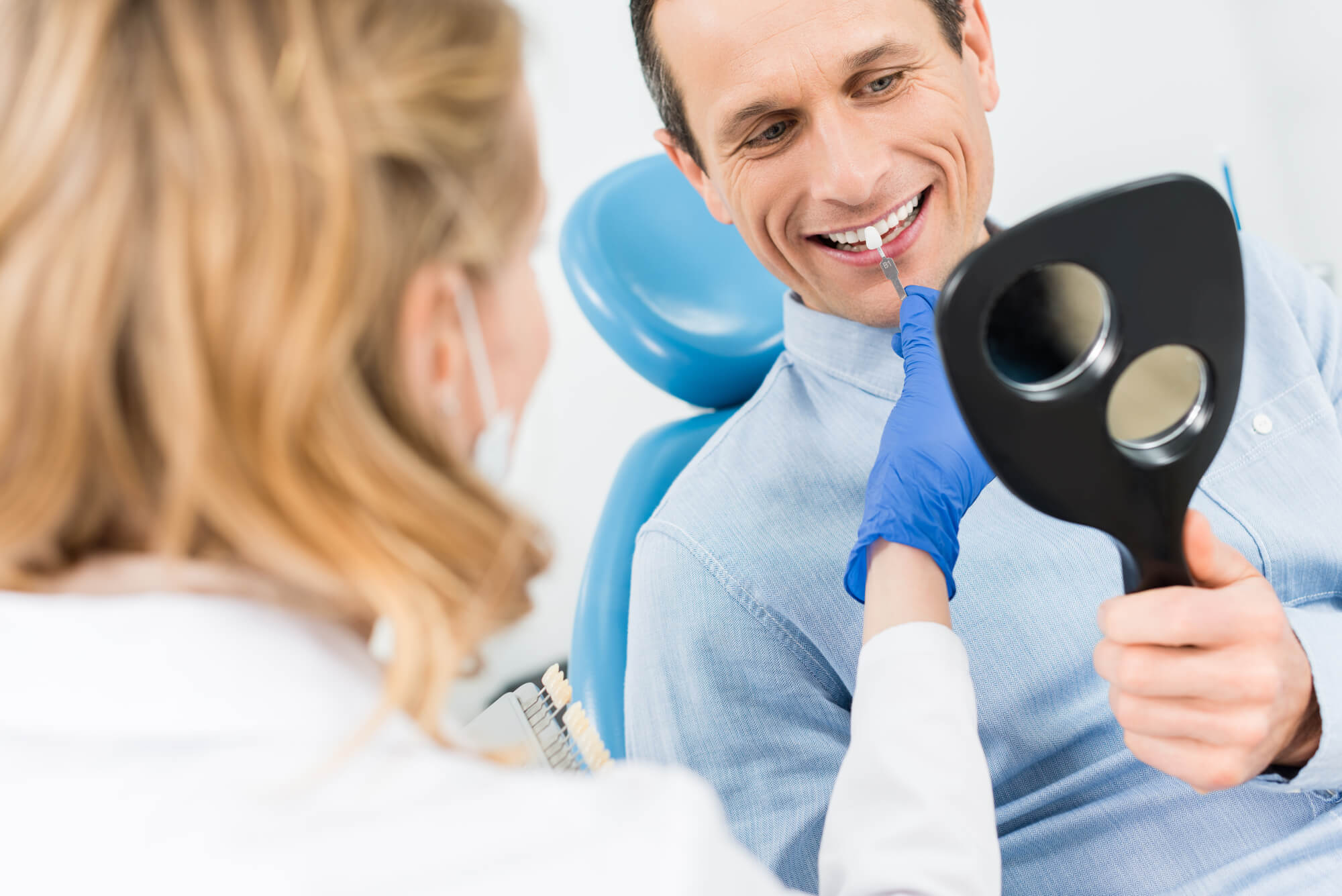 A general dentist in aurora coholding a tooth sample to a patient's teeth
