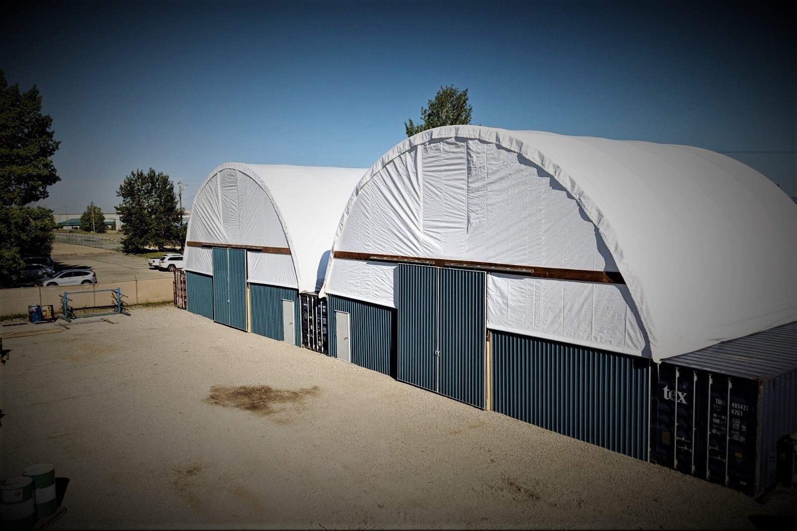 completed fabric building with two shipping containers and an industrial tarp roof