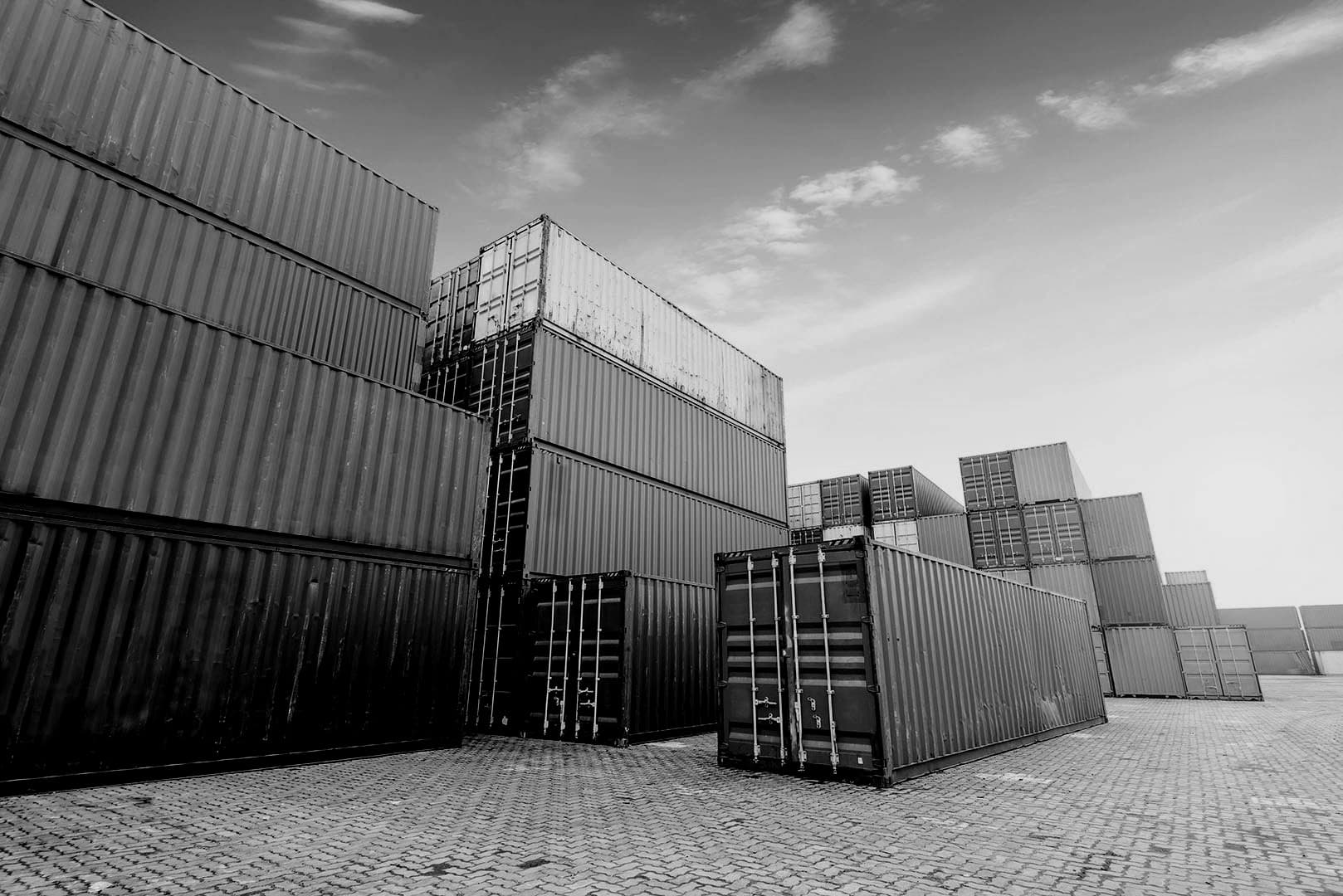 stacked shipping containers and large machinery in an industrial yard