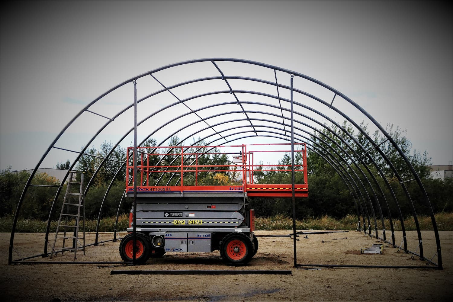 fabric building setup showing exposed HSS steel frame and machinery
