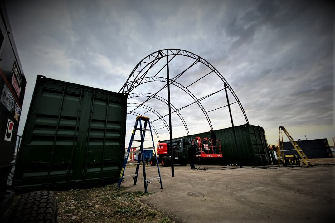 fabric building setup showing shipping container and exposed HSS steel frame