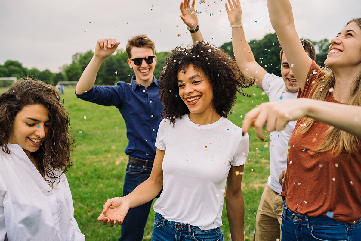 A group of friends dances and celebrates together outside, all smiling and laughing.