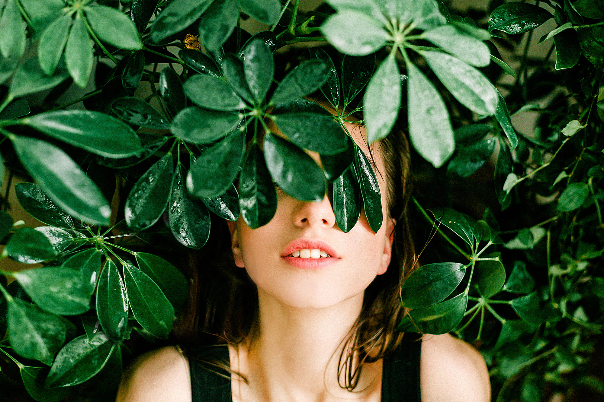A woman lays in green lush plants, with her face partially obscured by leafs.