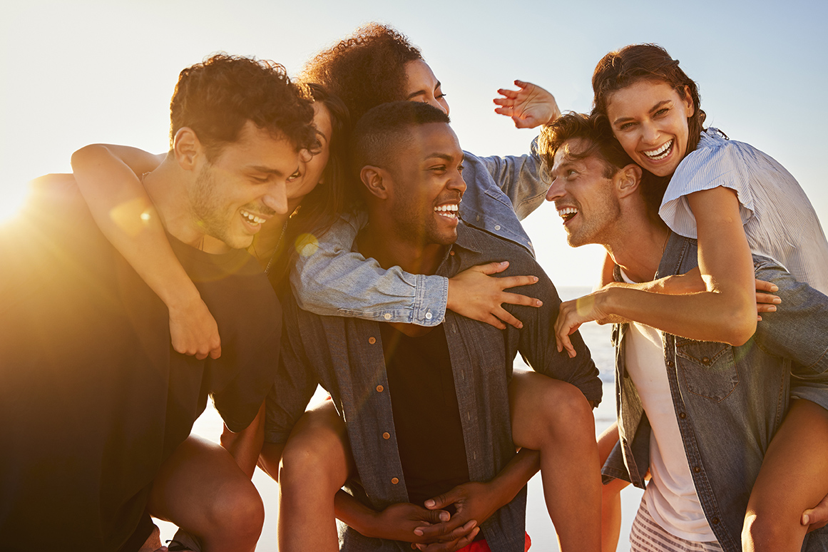 A group of friends hang out in the sun, smiling and laughing together.