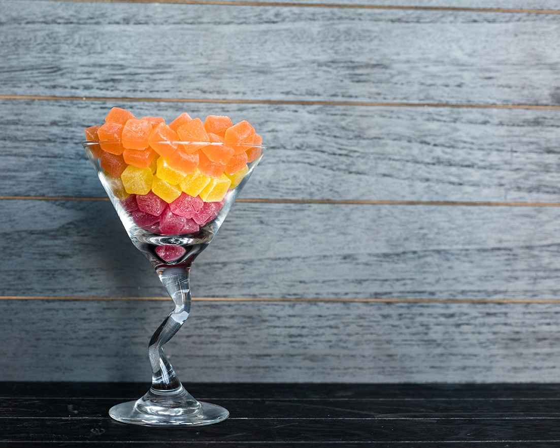 A martini glass full of cannabis gummies sits against a grey wood background.