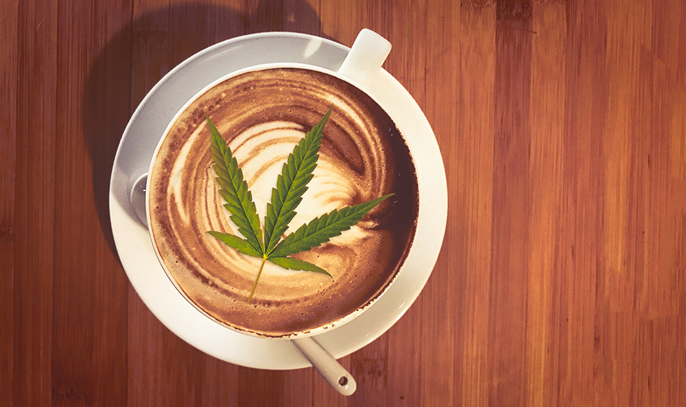 A coffee beverage is topped with a cannabis leaf.
