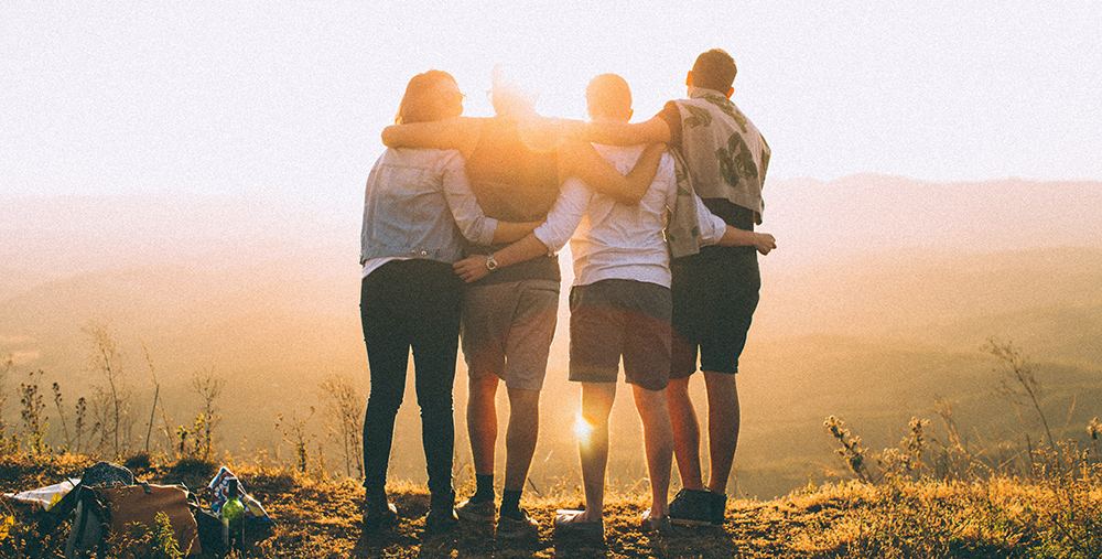 A group of four people watch the sunset on a mountain top with their arms around each other.