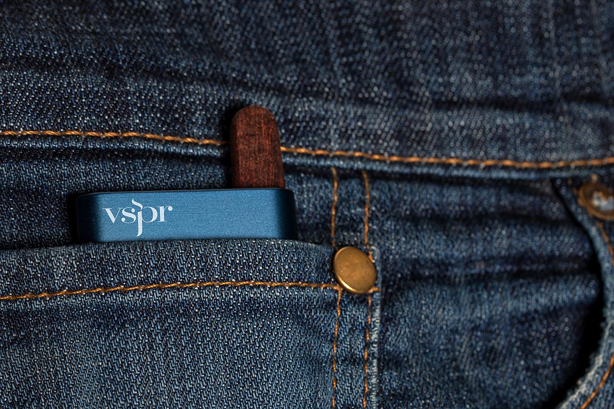 A closeup of a vspr vape cartridge in someone's jean pocket.
