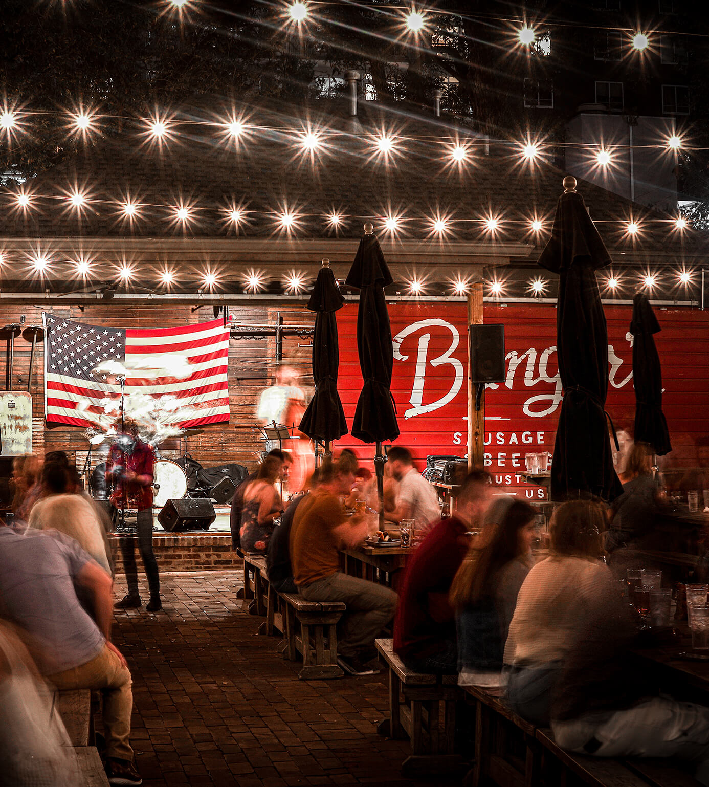 Night life image of Banger's in Austin Texas with people eating at picnic tables with hanging lights