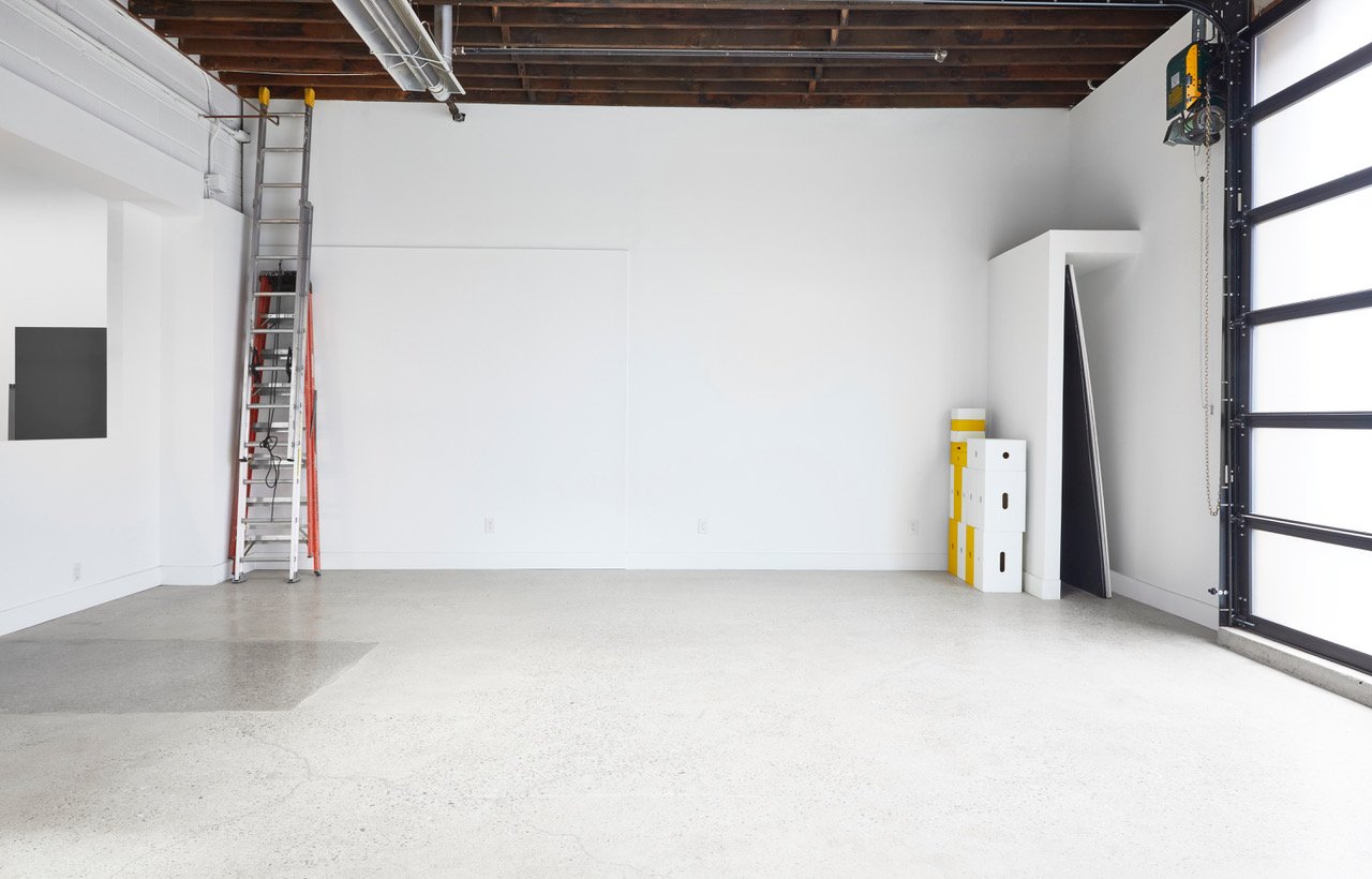 Open photo studio with garage door and white walls.