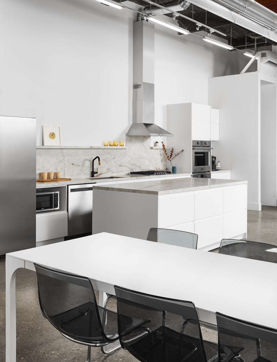 A modern kitchen studio with light counters and stainless steel appliances.