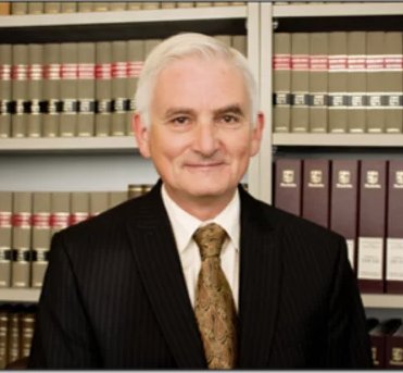 Headshot of Bob Arthur, lawyer in front of shelve of books and binders