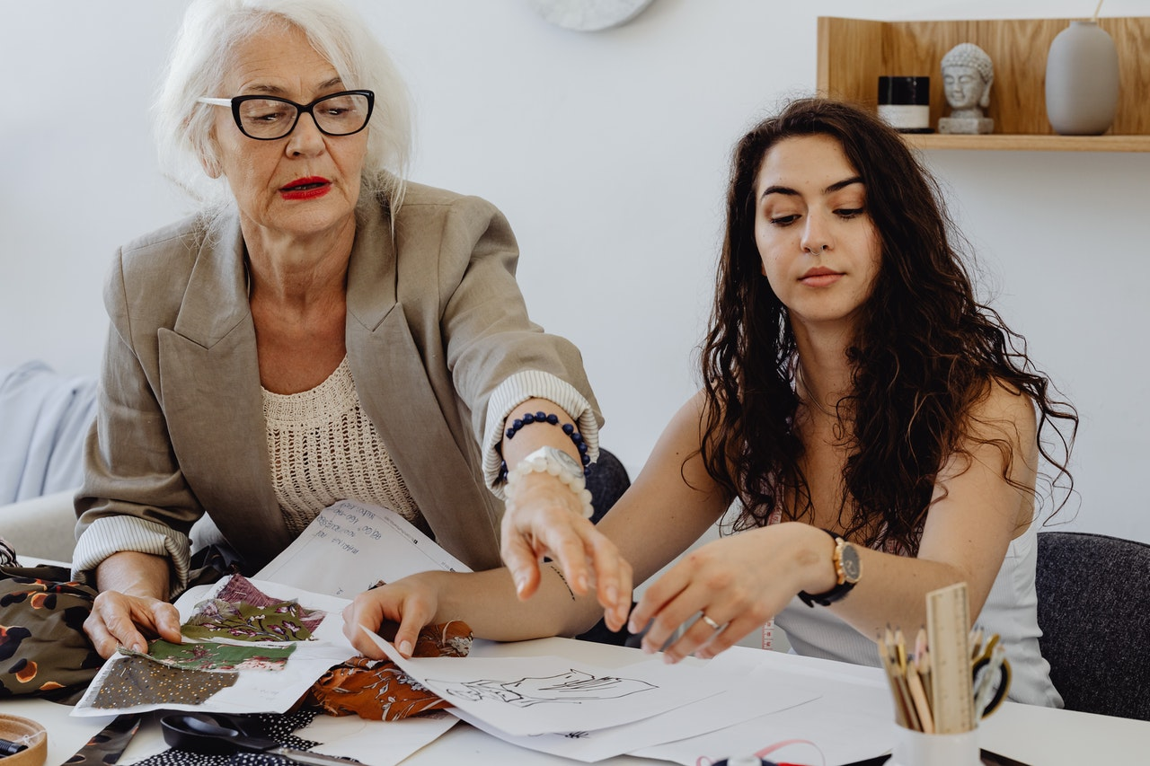 Multi generational family business, two women, one older, one younger discussing new clothing designs