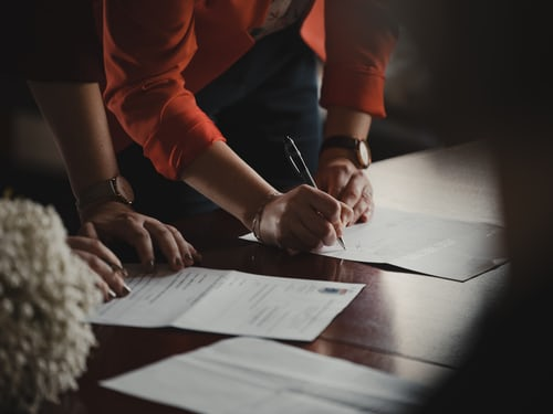 Person filling in documents while standing