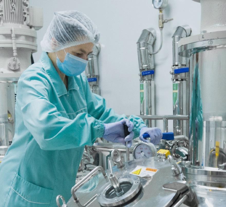 Employee watching pharmaceutical tanks