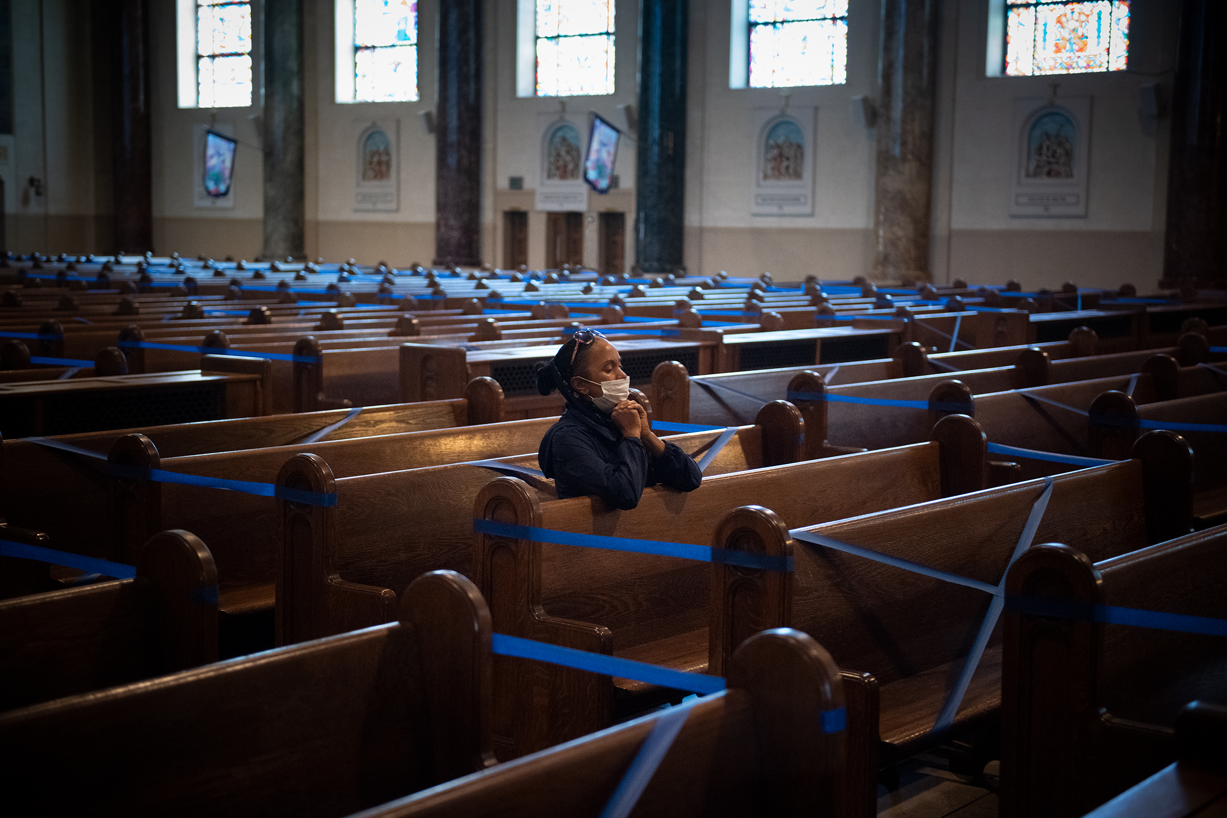 A woman prays alone, amid taped-off pews to comply with social distancing guideline. [Jeff Bruno]