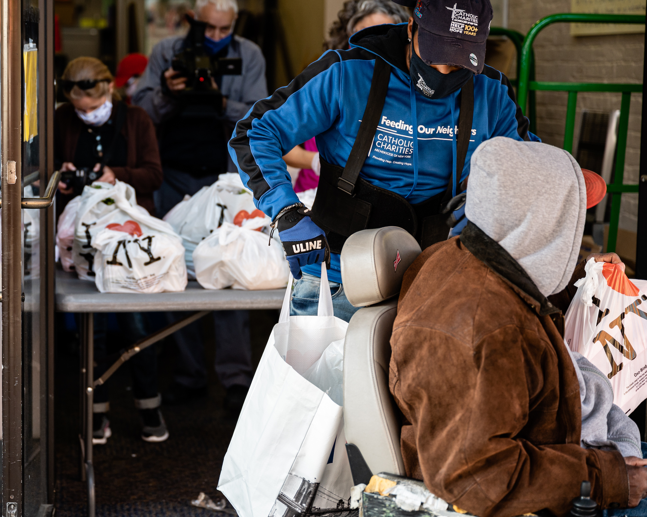 Workers at Catholic Charities in the Bronx distribute food to those in need. Throughout the pandemic, the archdiocese served vulnerable communities through 188 pop-up pantries in parishes and other locations, as well as provided more than 1 million meals were distributed by November 2020. [Johnny Zhang]