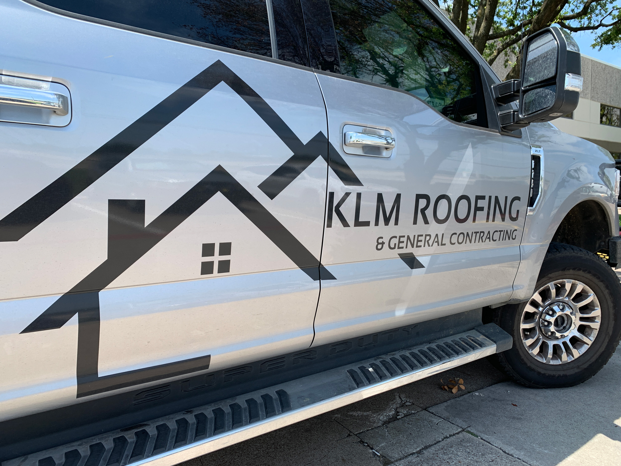 Side angle view of silver truck with KLM Roofing logo in black on the side.