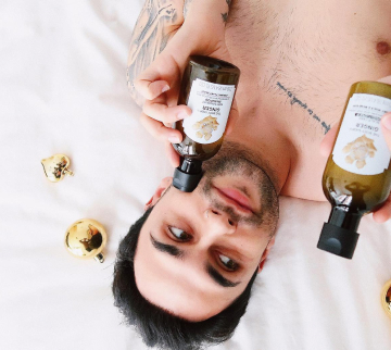 Influencer man laying on bed with products