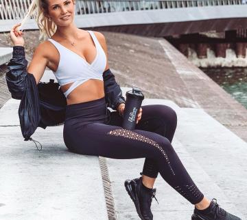 Sportive girl posing with shaker