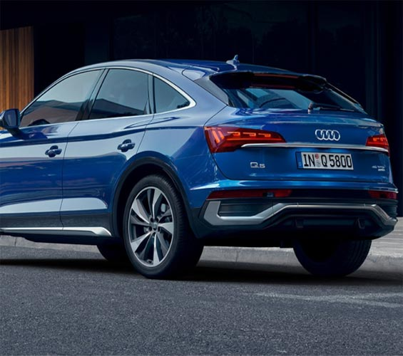 blue Audi parked on the side of the road