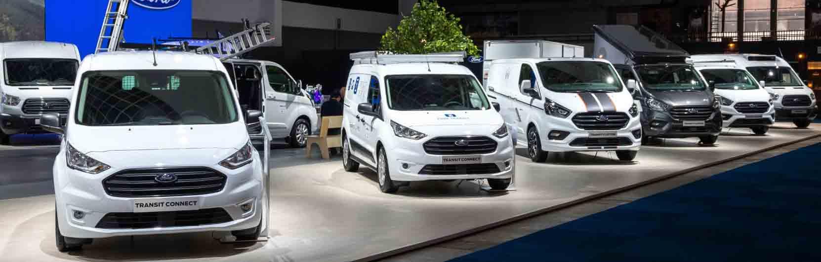 line of white vans on the showroom floor