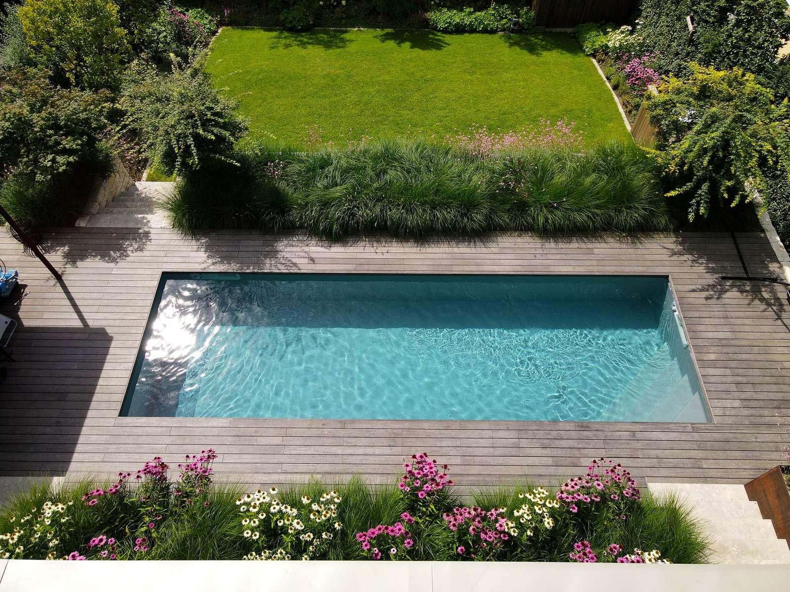 Modernes Magiline Schwimmbecken am Hang mit ansprechender Begrünung